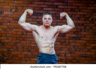 Strong Athletic Man Fitness Model Torso showing six pack abs. on the background of red brick wall