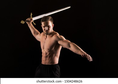 Strong athletic man showes naked muscular body. Studio shooting on a dark background.