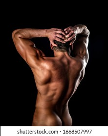 Strong Athletic Man showing his perfect back isolated on black background. Naked man posing in the studio on a dark background. Naked bodybuilder back. It's great
