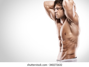 Strong Athletic Man  showing muscular body and sixpack abs over clean background