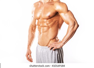 Strong Athletic Man showing muscular body and sixpack abs over white background.Muscular bodybuilder guy doing exercises with dumbbells over white background.Muscular man on white background