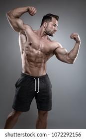 Strong Athletic Man zeigt Körper- und Bauchmuskeln auf grauem Hintergrund