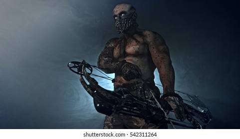 Strong athletic man standing with a bloodied bodybuilder bow in the dark and smoke. horror
