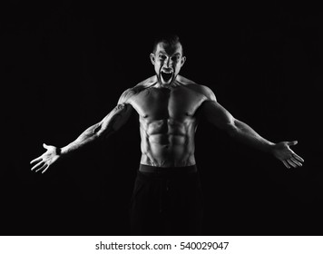 Strong athletic muscular man scream. Emotional male portrait. Half naked with six pack abs bodybuilder. Fitness model. Monochrome, black and white