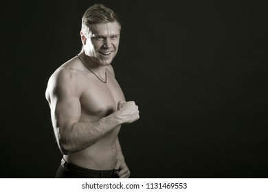 Strong athletic person, bodybuilder. Naked torso, muscular body. Studio shot on a black background, low key. The concept of bodybuilding,