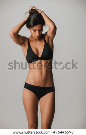 4ebdbb43c10 Strong athletic tan woman in black under garments ties her hair in a bun