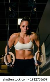 Strong, athletic woman on gymnast rings, looking at camera, closeup shot