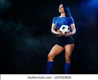 Strong athletic woman with soccer ball on black background. Sport concept. Football fan.