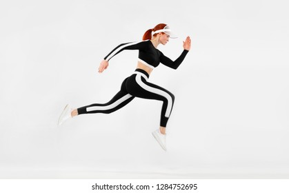 Strong athletic woman sprinter, running on white background wearing sportswears. Fitness and sport motivation. Runner concept with copy space.