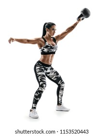 Strong athletic woman swinging a kettlebell. Photo of latin woman in fashionable sportswear isolated on white background. Strength and motivation. Full length