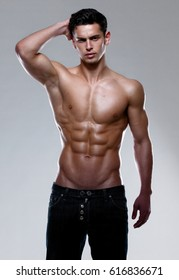 A strong athletic young man model showing six pack abs, holding his hand behind head. Vertical studio shot.