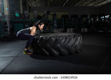 Strong Athletic young woman lifting a large tire , in the dark gym background. The athlete pushes a large wheel. Exercise with heavy weight in the gym.