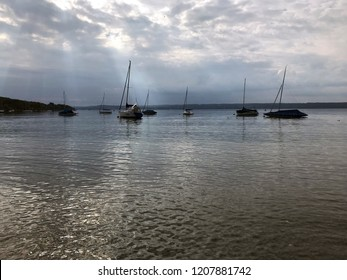 Strong autumn sun breaking through the cloudy ceiling at lake Ammersee in Bavaria, Germany