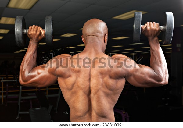 Strong back and shoulders on a  ripped lean muscle fitness man lifting weights.