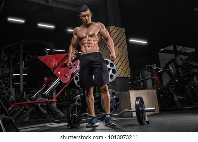Strong bald bodybuilder with six pack. Bodybuilder man with perfect abs, shoulders,biceps, triceps and chest, personal fitness trainer flexing his muscles