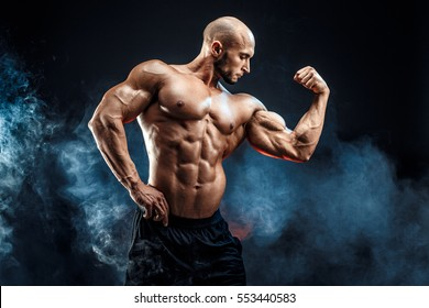 Strong bald bodybuilder with six pack. Bodybuilder man with perfect abs, shoulders,biceps, triceps and chest, personal fitness trainer flexing his muscles in blue, red smoke