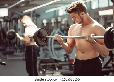 Strong bearded caucasian man at a crossfit gym lifting a barbell.