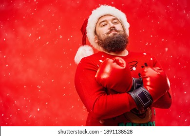 Strong bearded hipster man wearing Santa's hat and boxing gloves looking at the camera with confidence. Red background with the snow and copy space.
