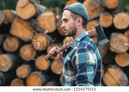 501e20a0a72 Strong bearded lumberjack holds ax on his shoulder on warehouse of logs