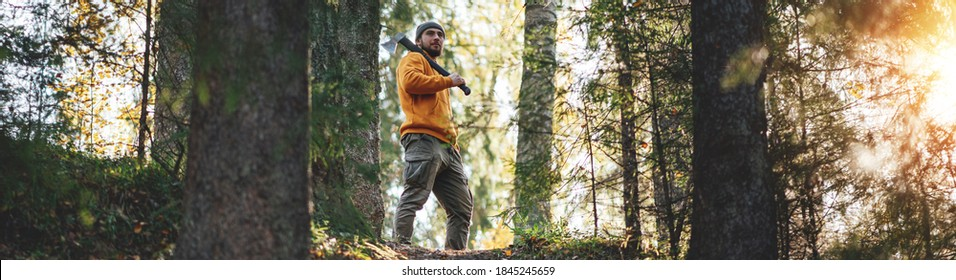 Strong bearded lumberman wearing work clothes holds axe on his shoulder. Wide image