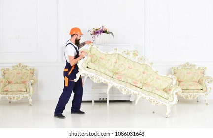 Strong bearded man lifting beautiful vintage sofa. Worker moving antique furniture isolated on white background. Home renovation concept.