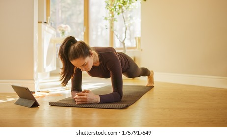 Strong Beautiful Fitness Girl in Workout Clothes Does Stretching Yoga Exercises at Home, Uses Digital Tablet for Online Exercise, Workout, Streaming Fitness. Home Sport Exercise in Bright Living Room