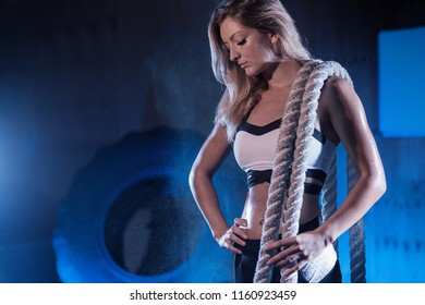 Strong beautiful woman with a battle rope on her shoulder in the gym. Young girl posing with gymnastics rope. Workout in fitness gym.