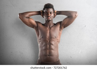 Strong black man posing in studio on textured background