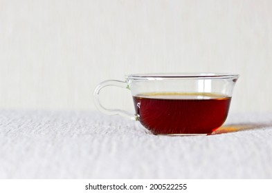 Strong black tea in glass cup on textured linen background. Selective focus. Object at the right part of image