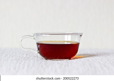 Strong black tea in glass cup close up on textured linen background. Selective focus. Object at the center part of image