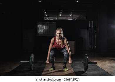 Strong blonde woman exercising with barbell in gym. Cute girl preparing for weightlifting workout. Sports, fitness concept.