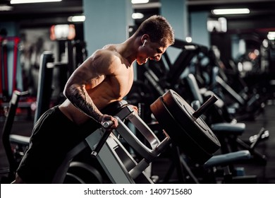 Strong Bodybuilder Doing Heavy Weight Exercise For Back On Machine. T-pull exercise.