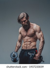 Strong bodybuilder with dumbells and naked torso posing in studio