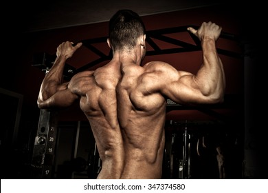 Strong bodybuilder in the gym doing pull ups