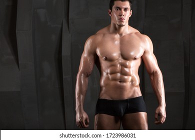 Strong bodybuilder man on dark background. Concept of healthy lifestyle.
