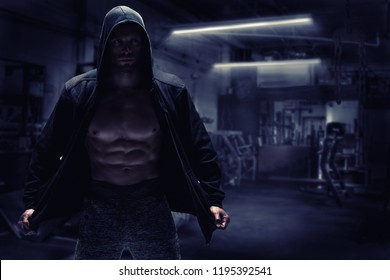 Strong bodybuilder man pumping up muscles after extreme workout . Bodybuilding concept background.