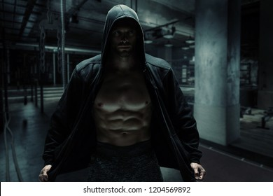 Strong bodybuilder man pumping up muscles after extreme workout in dark grunge gym . Bodybuilding concept background.