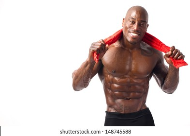 Strong bodybuilder man smiling with perfect abs, pecs, shoulders,biceps, triceps and chest holding a red towel. Isolated on white background.