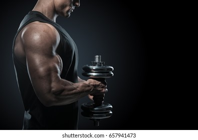 Strong bodybuilder with perfect deltoid muscles, shoulders, biceps, triceps and chest. Close-up of a power fitness man. Handsome power athletic man in training pumping up muscles with dumbbell.