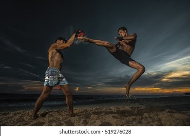 Strong boxer doing back leg high kick during kickboxing exercise with trainer at sunset