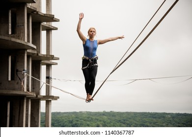 Strong and brave woman balancing on a slackline against the background of high empty building on summer day