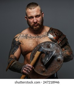 Strong brutal male with beard holding shield and axe