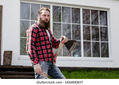 Strong brutal man with a beard dressed in a checked shirt standing with an ax in the hand against the background of the house with a large window