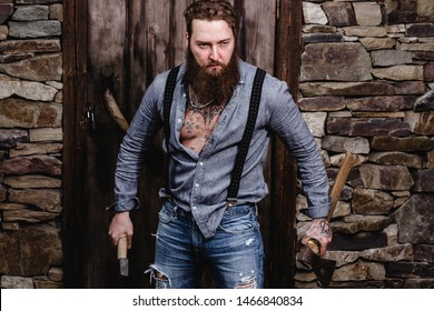 Strong brutal man with a beard and tattoos on his hands dressed in stylish casual clothes stands with two axes in his hands on the background of stone wall and wooden door