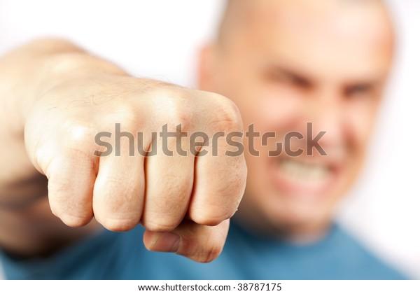 Strong built aggressive man punching towards the camera