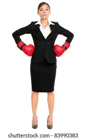 Strong business woman boss executive concept. Businesswoman standing intimidating wearing boxing gloves ready for the competition. Confident attitude by young mixed race female model in suit.