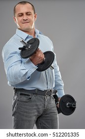 Strong businessman training with dumbbells on gray background