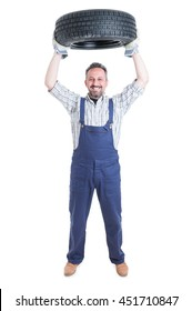 Strong cheerful engineer in blue overalls holding tire above head isolated on white background