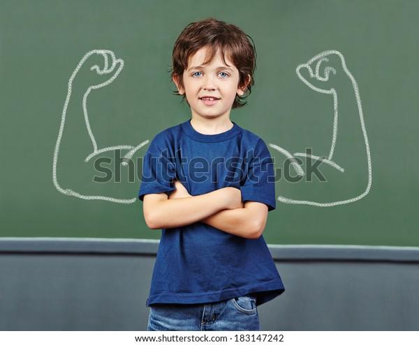 Starkes Kind mit Muskeln, die in der Grundschule auf der Tafel gezogen werden