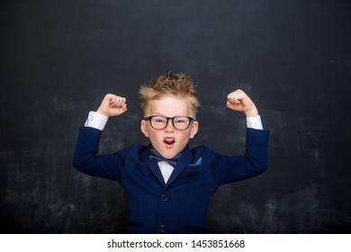 Strong child with muscles on chalkboard dreams to be a businessman. Nerd school boy in glasses showing bicep muscles. Strong, confidence, success, possible, innovation. Go back elementary school
